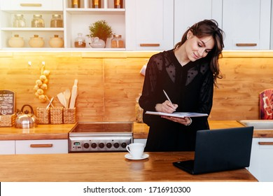 Working mom with makeshift office set up in the kitchen wearing black dress