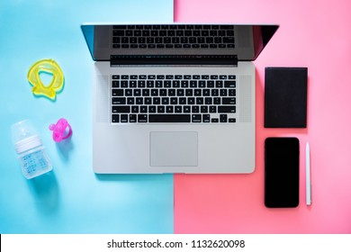 Working mom top view flatlay of workplace baby items and laptop with phone