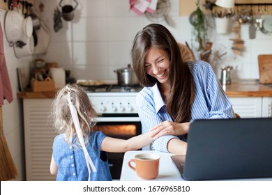 Working mom works from home with kid. Happy mother and daughter have fun. Successful woman and cute child using laptop. Freelancer workplace in kitchen. Female business. Lifestyle authentic moment