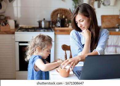 Working mom works from home office with kid. Woman and cute child using laptop. Freelancer workplace in cozy kitchen. Happy mother and daughter. Female business, empathy, care. Lifestyle family moment