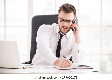 Working moments. Handsome young beard man in shirt and tie working at his working place
