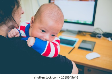 Working mother with a baby and her computer