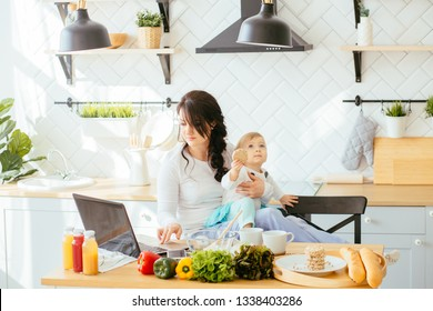 Working mother concept. Busy mm with baby in kitchen. Mother working at home. Super mom multitask woman. Mommy bsinesswoman. Multitasking and husework.