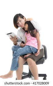 Working mother and daughter with tablet are sitting on office chair