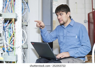 ?echnician is working with notebook in server's room