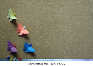Working office board of cork and colored butterflies from origami