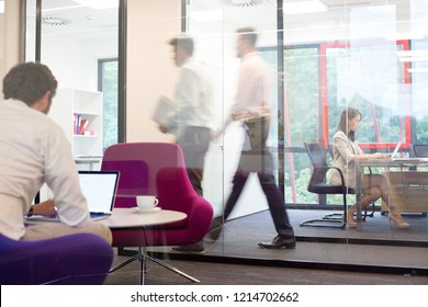 A working office with people walking out of focus, concept of a real life busy office environment