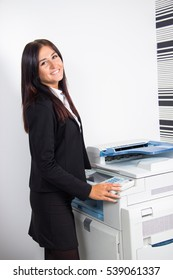 Working in the office. Woman standing by an office printer.