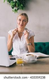 Working on caffee break. Woman wearing eye glasses.
