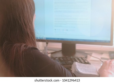 Working on computer. Unrecognizable young woman browsing internet pages in screen. Back view.