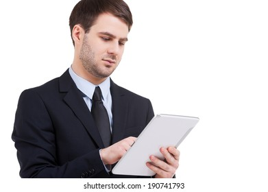 Working on digital tablet. Confident young man in formalwear working on digital tablet while standing isolated on white