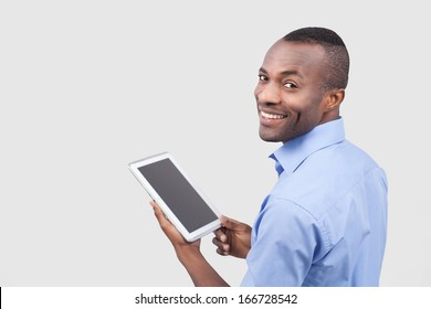 Working on digital tablet. Rear view of young African man working on digital tablet and looking over shoulder while standing isolated on grey