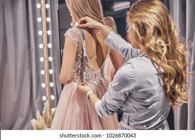 Working on dress.  Young woman measuring bride while standing in the fitting room