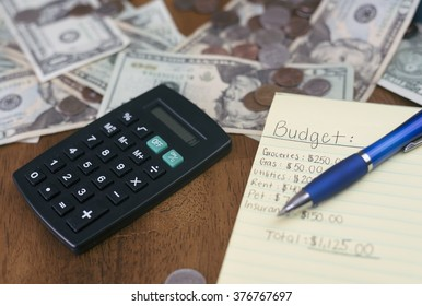 working on household finances, with budget written on paper with money and calculator.