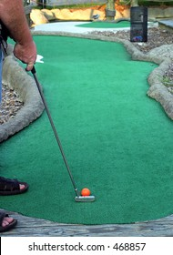 Working On My Putt.. a man playing miniature golf