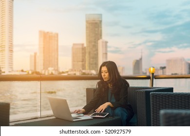 Working on new project. Asian woman with laptop in background of river beautiful view at sunset and background blur building skyscrapers. (advertise concept)