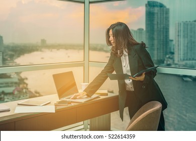 Working on new project. Asian woman with laptop in background of river beautiful view at sunset and background blur building skyscrapers. (vintage color tone, advertise concept)