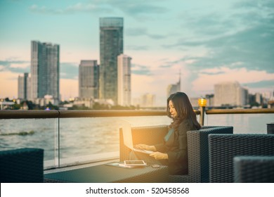 Working on new project and Having opportunity to work everywhere. Asian woman with laptop in background of river beautiful view at sunset and background blur building skyscrapers. (advertise concept)