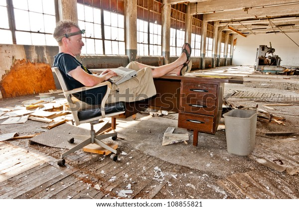 Working on an old computer at a desk inside an abandoned factory.