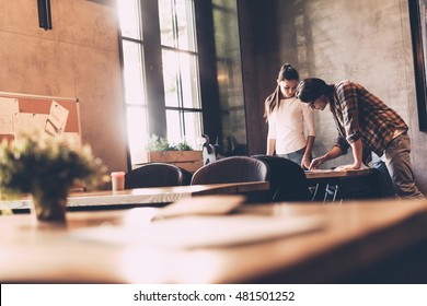 Working on project together. Confident young man and woman working together while standing near the desk in creative office