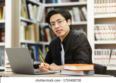 Working On Research Project. Portrait of asian male student using laptop at library, writing in notepad, looking at camera