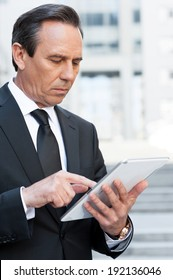 Working on tablet. Confident senior man in formal wear working on digital tablet while standing outdoors