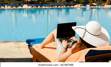 Working on travel, girl in a white hat with a laptop near the pool. Work on vacation, work on vacation.
