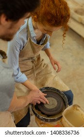 Working on wheel. Curious ginger girl sitting on a chair and learning pottery wheel technique with assistant of dark-haired master