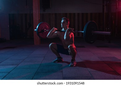 Working out by lifting weights in a cross-training gym. Muscular powerful man with heavy barbell doing squat exercise in red blue neon light