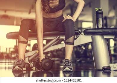 Working out with dumbbell weights at the gym.Fitness Women exercising are lifting dumbbells with a whey protein placed next to the gym.Fitness muscular body.Workout at gym.