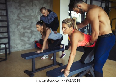 Working out in fitness center with trainer supervision