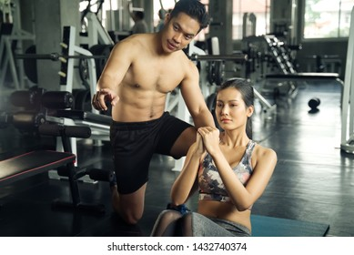 Working out at GYM concept. Young Asian handsome man giving some advice to young pretty girl working out her abdominal muscles by sit ups in GYM. Health and fitness concept.