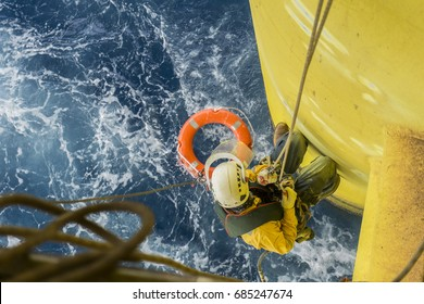 Working overboard. A commercial abseiler with fall arrestor device and safety precaution doing inspection on oil and gas jacket module.
