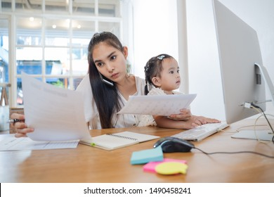 Working Parents at home,Busy Asian Woman mom working with Daughter at house