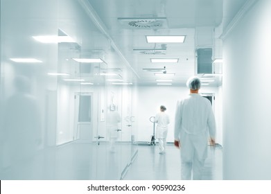 Working people with white uniforms in modern  factory environment