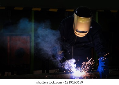 Working person About welder steel Using electric welding machine There are lines of light coming out and safety equipment.