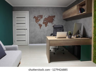 Working place on grey wall with map of the world.lap top and stationary computer. Interior.
