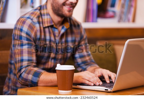 Working with pleasure. Close-up of young man working on laptop and smiling while sitting at the desk with bookshelf in the background
