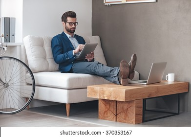 Working with pleasure. Handsome young man keeping legs on table and working with touchpad while sitting on the couch in office