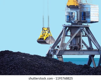 Working port crane and bucket, loading of coal. Marine loading terminal, trading port.  Grapple crane and pile of hard coal against the sea and blue sky