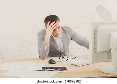 Working problems, issues of business. Young businessman in white modern office interior, thoughtful, sitting at computer table.