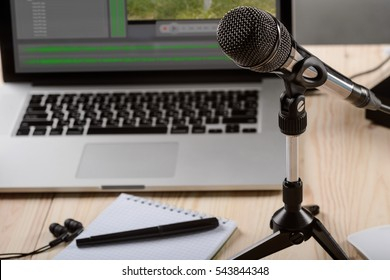 The working process of a blogger. Modern laprtop with special programme for cutting the reviews and video editing. Expensive microphone with a holder and stationery.