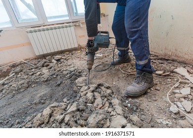 Working process of dismantling and disassembling the floor with construction electric perforator in room of apartment is that under construction, remodeling, renovation, extension, restoration and