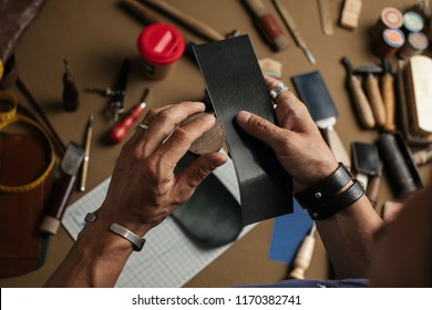 Working process of hand made leather wallet production in the leather workshop. Male hands close up holding crafting tool and working with leather.