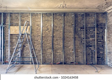 Working process of installing metal frames for plasterboard (drywall)   gypsum walls with ladder and tools in apartment is under construction, remodeling, renovation, extension, restoration