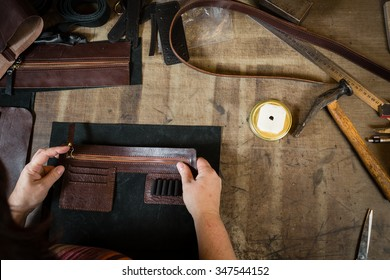 Working process of the leather bag or messenger in the leather workshop. Woman's hands holding the leather. Color tone image. View from above.
