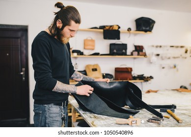 Working process of the leather bag in the leather workshop. Crafting tool on work table background.