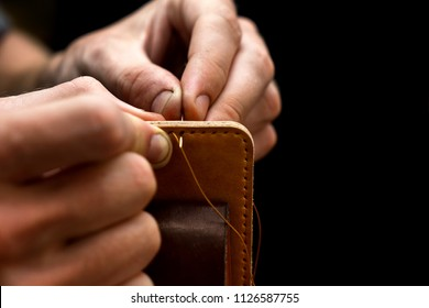 Working process of the leather belt in the leather workshop. Man holding crafting tool and working. He is sewing to make a walet. Tanner in old tannery. Wooden table background