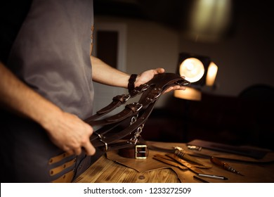Working process of the leather belt in the leather workshop. Man holding photographer's belt for camera. Tool on wooden background. Tanner in old tannery. Close up master's arm.