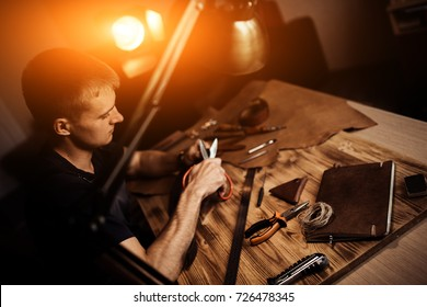 Working process of the leather belt in the leather workshop. Man holding crafting tool and working. Tanner in old tannery. Wooden table background. Warm Light for text and design.